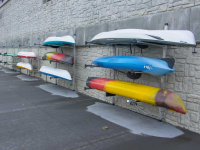Multiple wall-mounted storage racks for a kayak rental business