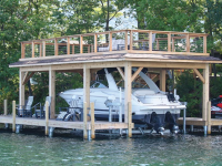 Boathouse with sundeck and boatlift on a permanent pile dock