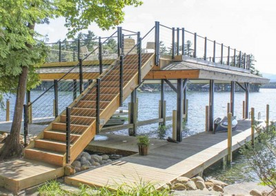 Pile dock with sundeck style boathouse with stainless steel cable rail