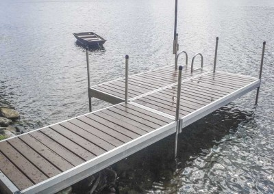 Medium duty aluminum leg docks with cedar decking, aluminum ladder and pipe-mounted flag pole