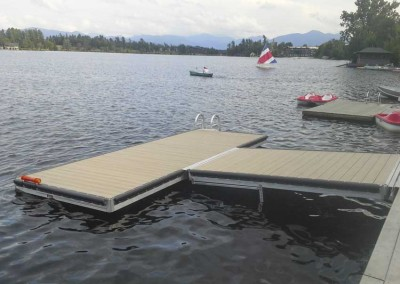T-shaped medium duty floating dock with float frame to support the ramp; the float frame is adjusted during installation based on the pitch of the ramp.