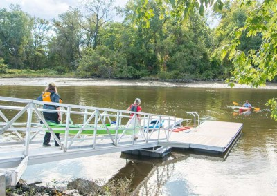 Aluminum gangway transitions from the shore to the floating kayak launch dock