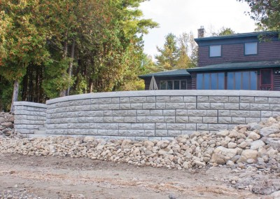 Stacked decorative concrete retaining wall and rip-rap erosion control