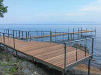 Curved shoreside platform with stainless steel cable rails