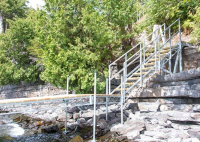 Steel stairs that traverse a rocky shoreline