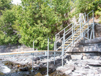 Steel stairs designed to transition over a rocky shoreline to our leg docks